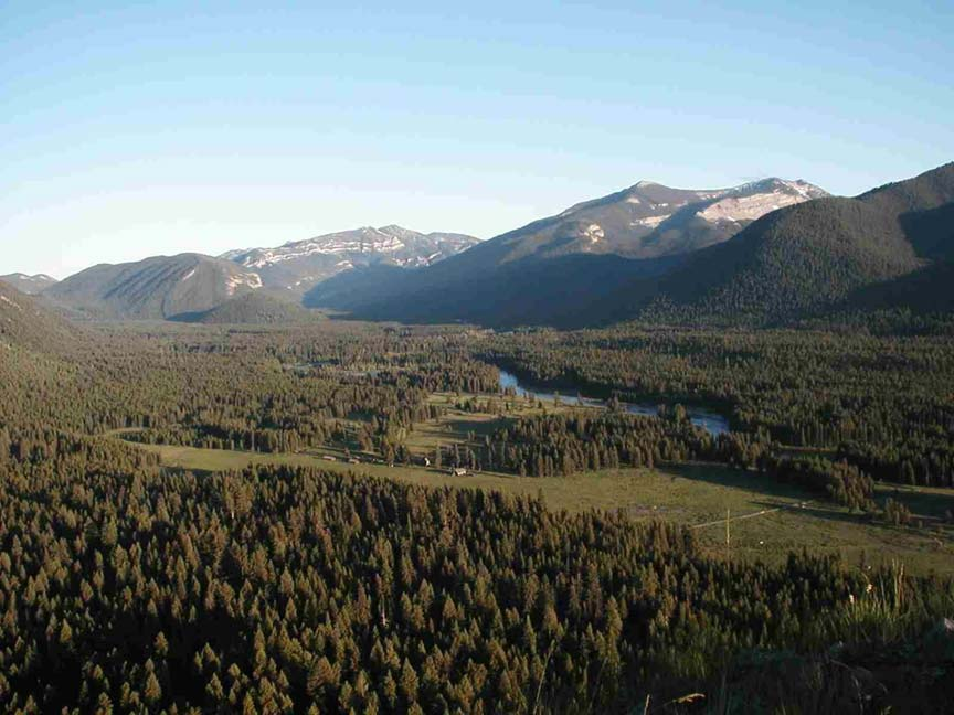 An aerial image of a wide forested river valley textured with large clearings. Low mountains rise on both sides of the valley in the background.