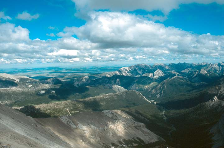 An open mountain landscape of countless peaks rising off into the distance, under a blue sky dotted with puffy white clouds.