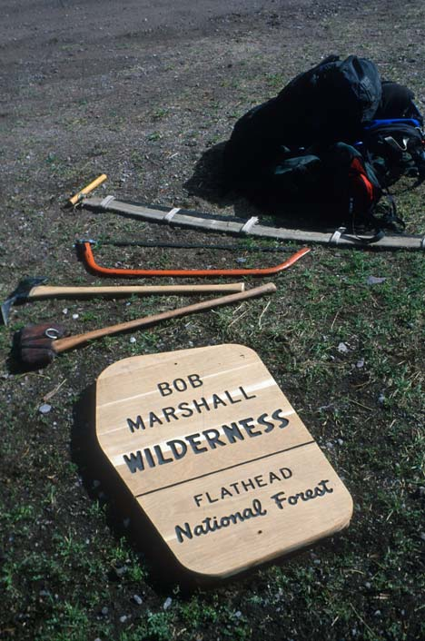 A new wilderness boundary sign lies on the ground, surrounded by various hand tools and a backpack.
