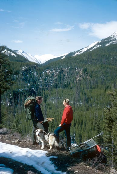 Two male backpackers and dog taking a break viewing mountain peak
