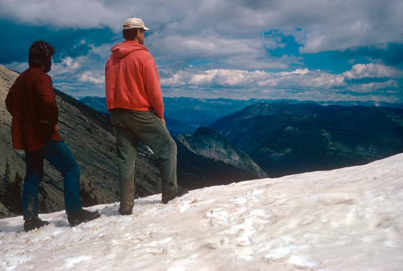 Two men in red jackets standing on a snowy ridge, overlooking the mountain valleys in the distance.