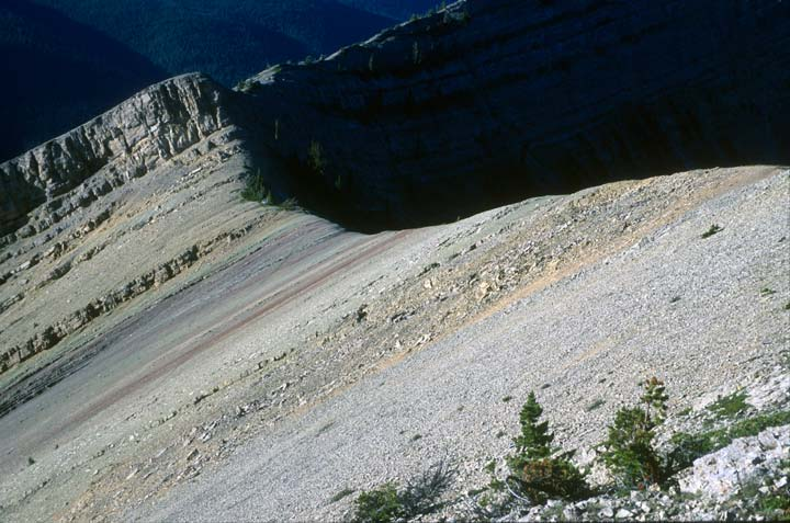 A bare gravel slope striped with red and orange mineral deposits, fading off into black shadow along the ridgeline.
