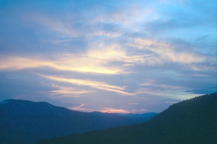 A painterly sunset of orange streaks on a background of blue, high above the black forest ridges below.