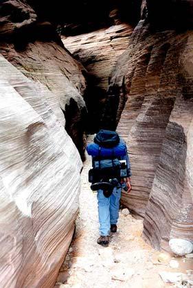 A backpacker enters a very narrow canyon.