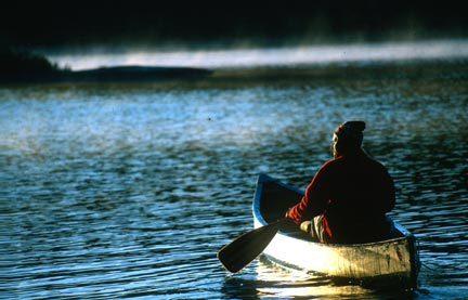Lone male canoer paddles across a tranquil lake at sunset.