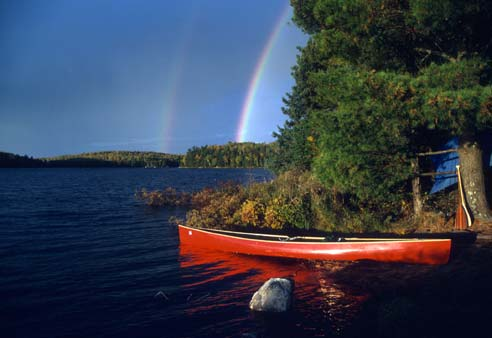 An iconic image of a bright red canoe pulled up along the shore of a large lake. The dark blue sky above is brightened by a double rainbow.
