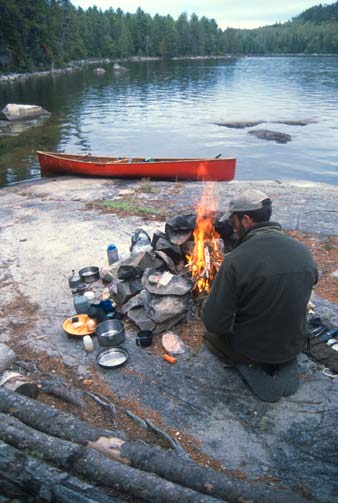 A man sitting next to a small campfire on a large rock, surrounded by equipment. A red canoe is tethered nearby, pulled up along the edge of the rock.