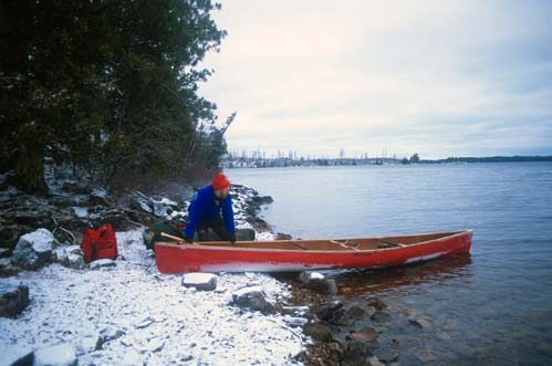 A man in a blue jacket stands along a snowcovered shoreline, pushing a red canoe into the frigid water.