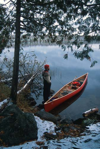 A man standing on a rock along the shore under a large tree. A red canoe floats next to him, reflecting off the mirror surface of the water.