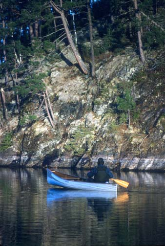 A person in a white canoe, paddling along a steep rocky shoreline.