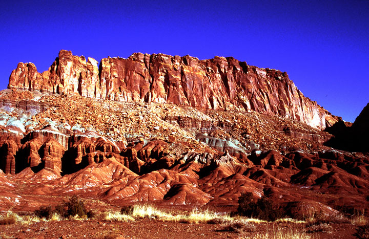 Brown dirt with patches of golden grass, roll into small ridges, which fade into a steep rocky slope, rising to a vertical rock face above, against a background of empty blue sky.