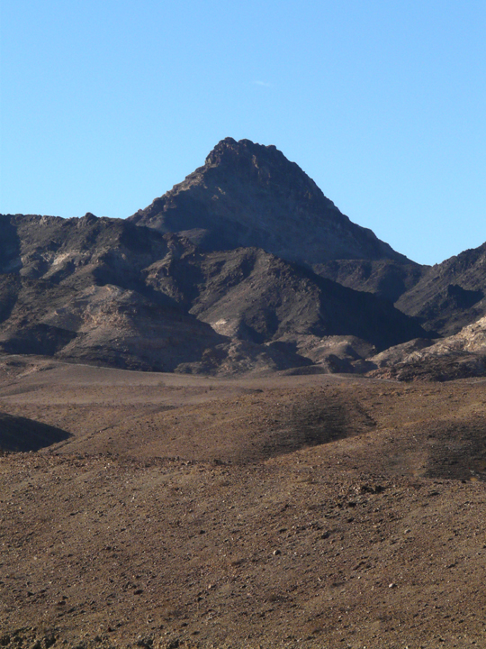 Brown sand and gravel stand as the front for a series of dry, dark cliffs under a blue sky.