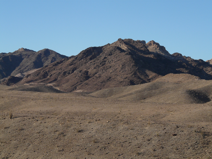 The hills are dark and dusty, and at their feet is only more brown dirt and dust.