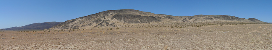 This panorama is made up of dusty gold and grey desert under a warm sun.