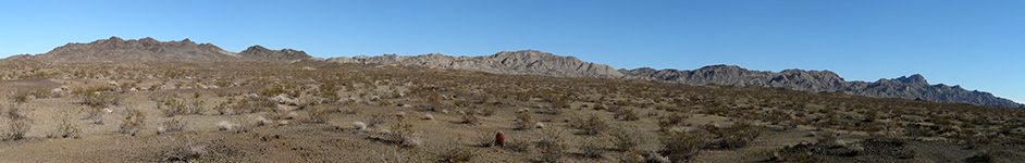 A panoramic shot of the desert, with a few scattered mountains in the distance.