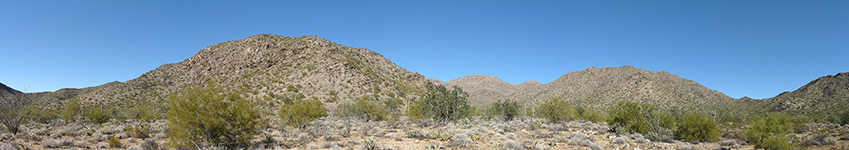 A shrub covered desert floor leads up to large barren rolling hills.