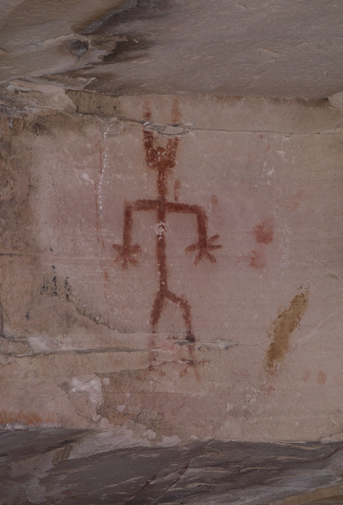 A pictograph drawn in redish-brown color on the side of a rock.