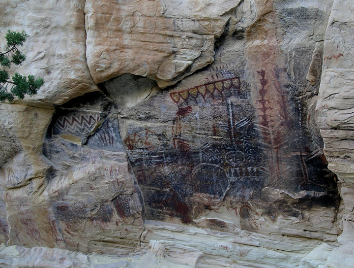 A mural of pictographs in different colors drawn on the side a large smooth rock.
