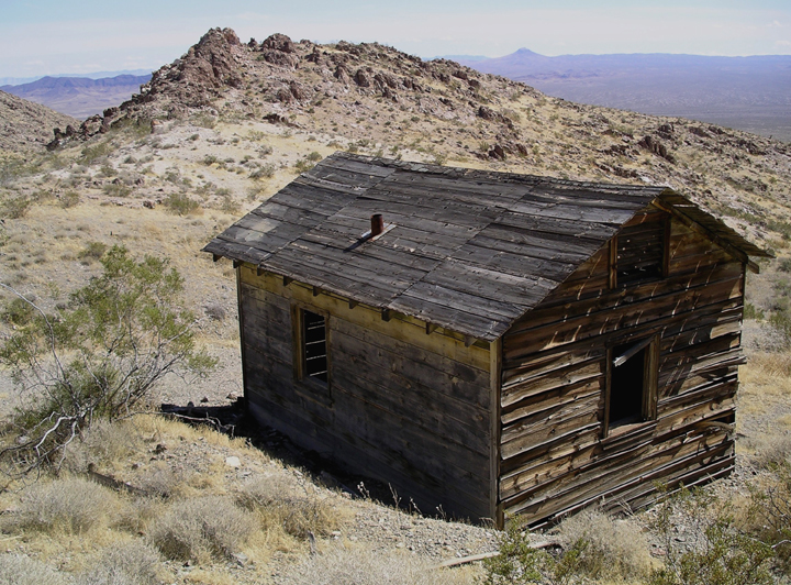 A dilapidated cabin in the desert, viewed from a top a rise.