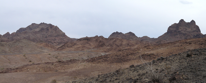 A sharp line of red rock outcroppings against a grey sky.