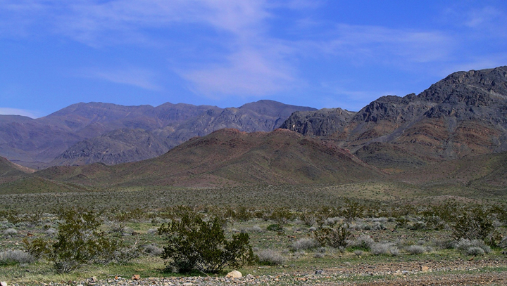 The hues in this photo are very bright greens, blues and reds.  The desert and hills are alive with color.
