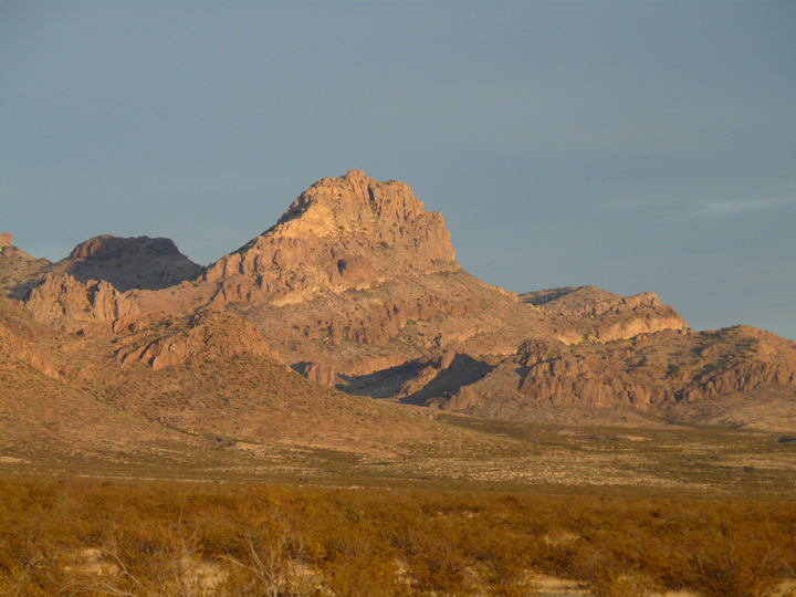 A vivid picture of desert mountains, painted gold by the light of a dying sun.