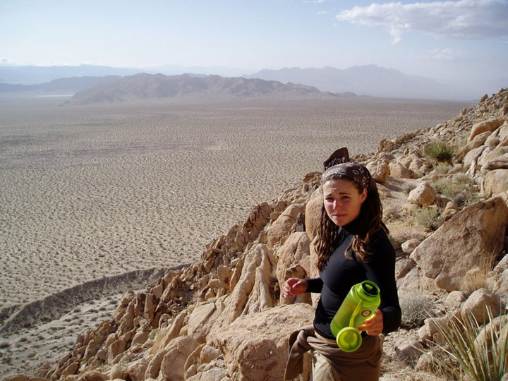 A girl turns back to offer her waterbottle to the photographer.  The view beyond is a rocky drop down to the desert below.