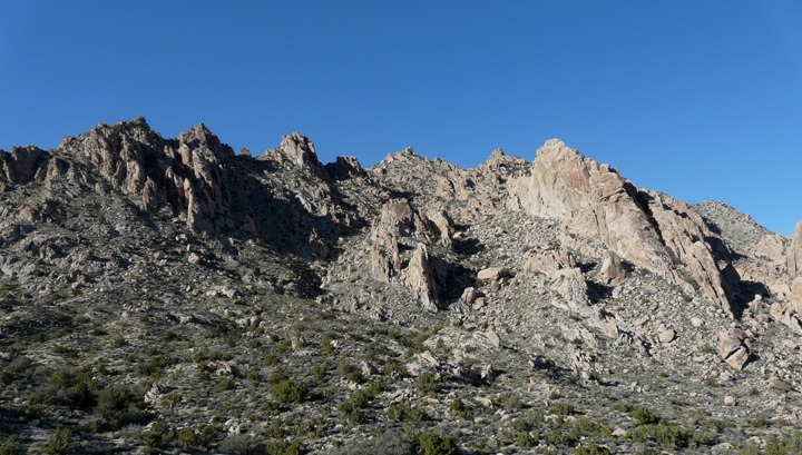 A panoram of rocky, grey ridge mountains.