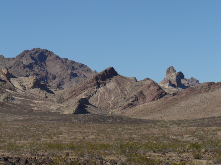 These strange mountains are painted all in shadows of faded red and grey.  Green dots the desert floor.