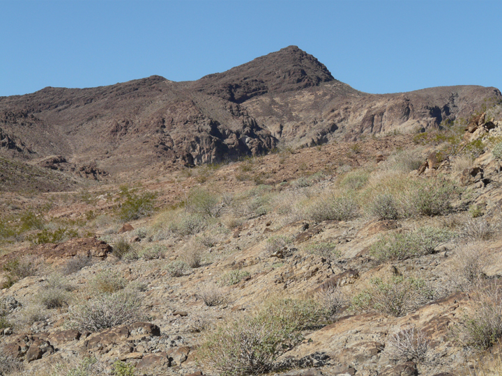 A gentle sweep of brush covered hills gives way to a strange rock outcropping.