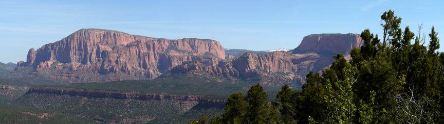 A ridge of red rock formations stands in the distance.  In the foreground is a strand of green trees.