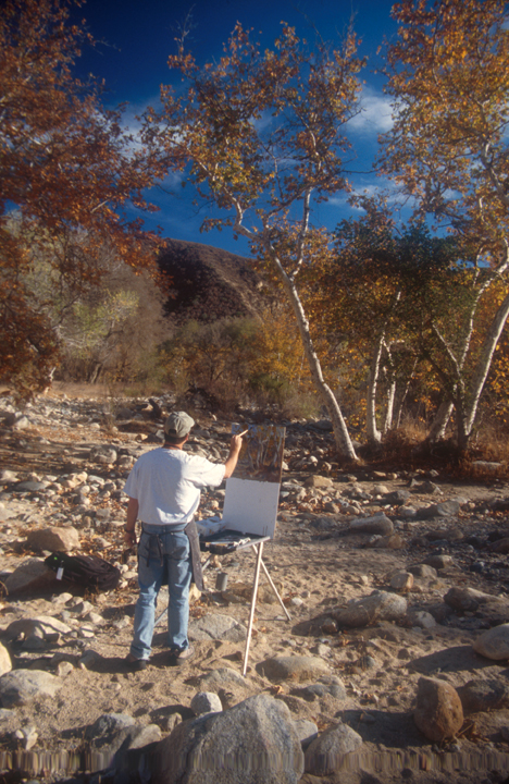 A painter is working to capture an autumn scene; he stands in a rocky riverbed looking at birch trees with yellow and red leaves.