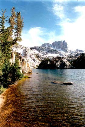 Looking down the shoreline of a crystalline alpine lake, a tall rocky summit laced with snow, rises from the far shore.