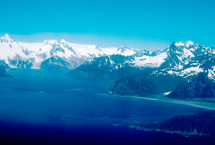 An aerial view overlooking tall snowcapped peaks, sweeping down to the blue waters of the deep fjords below.