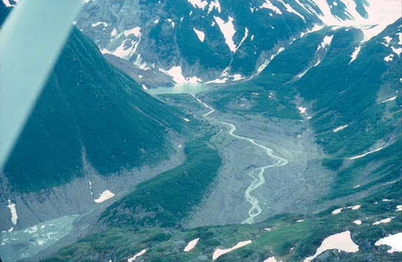 An aerial view of a high alpine valley mottled with spring snow, and cut by a small river flowing along the middle.