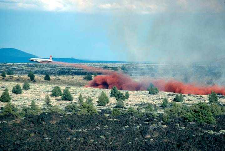 A large aircraft flying very low over the open landscape, trailing a cloud of red fire retardant.
