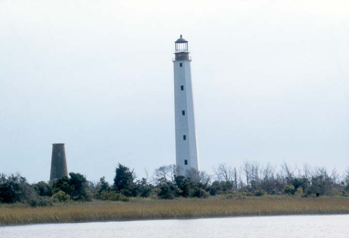 A tall slender white lighthouse, standing high above the trees along the marshy coast.