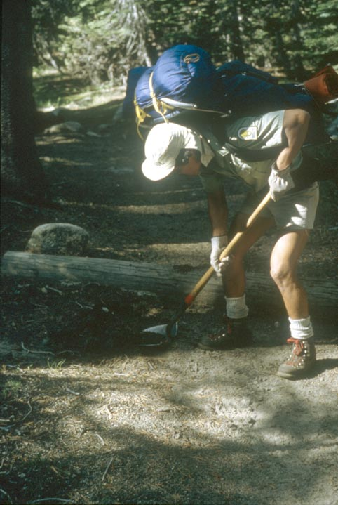 A man wearing a large blue backpack, scooping ashes from a fire-pit with a shovel.