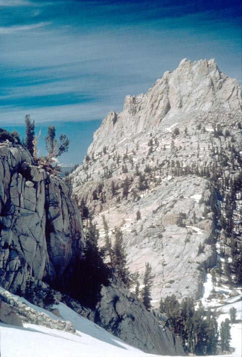 A jagged peak of barren rock rises in the background, sweeping down to a snowfield nearby.