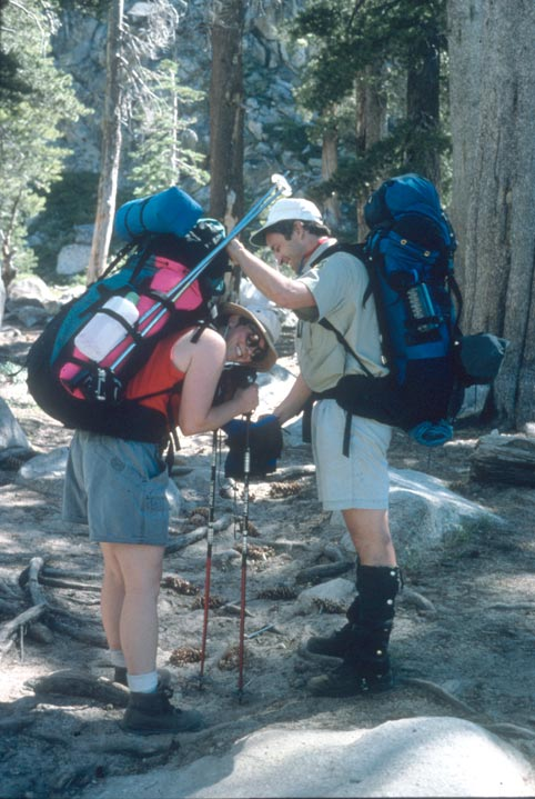 A man and a woman, both wearing large backpacks, standing along a trail, surrounded by large trees.