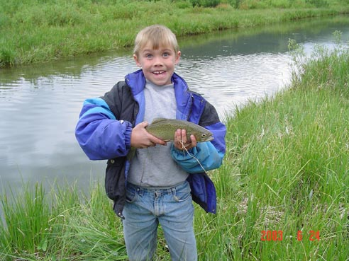 An excited young boy stands along the edge of a small stream, holding a trout in his hands.