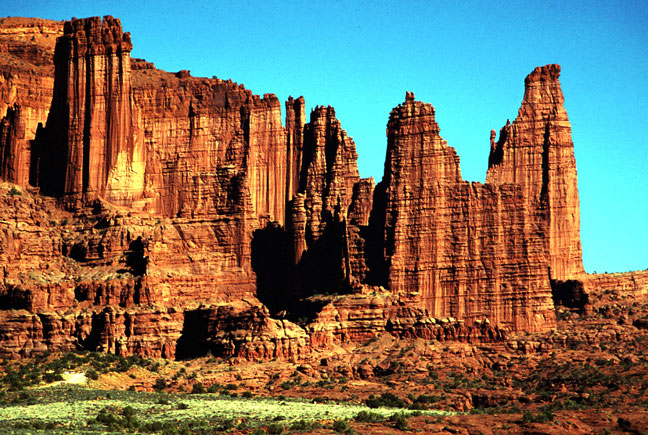 Massive sandstone faces and columns rise high over the desert floor below.