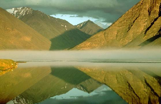 A perfect reflection of a mountain scene draped in morning light, rising above the thin layer of fog, over a placid lake.