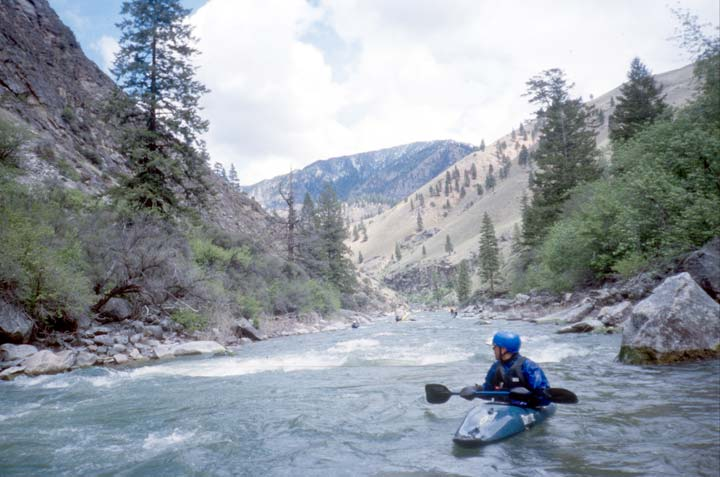 A kayaker in a blue kayak looking back down a small river, bordered by steep hills and forest.