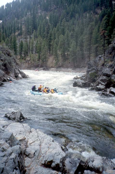 A large blue raft, running a section of whitewater through a canyon, bordered on either side by large jagged rocks.