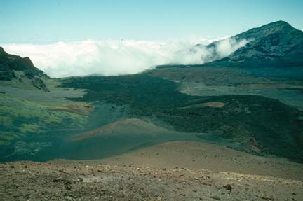 Looking out over a barren rocky volcanic landscape, to puffy white clouds rolling up the far mountains.