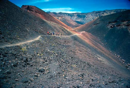 A small group of hikers traversing a narrow trail along the edge of a steep volcanic face of gray and red rock.