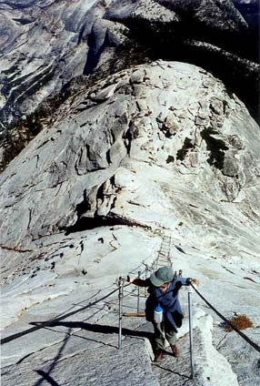 A hiker struggling up a section of cable railing, on a steep granite slope.