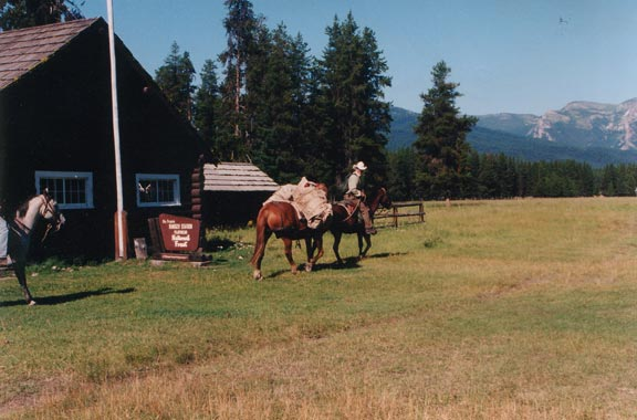 A man sitting on horseback near a ranger station. Mountains rise in the background, across a large open field.