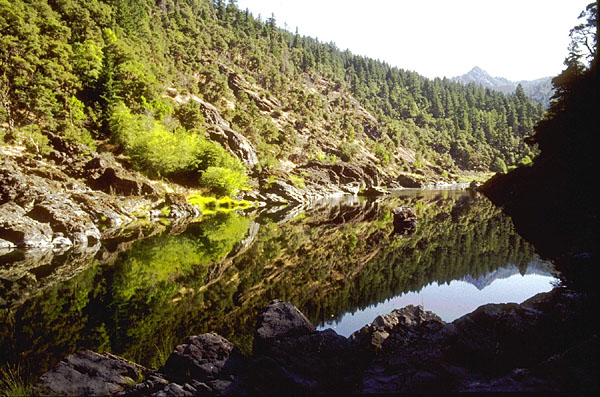 A narrow channel of placid water, the mirror surface reflecting the jagged rocky slopes on each side.
